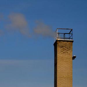 Skorsten som släpper ut rök mot en blå himmel.