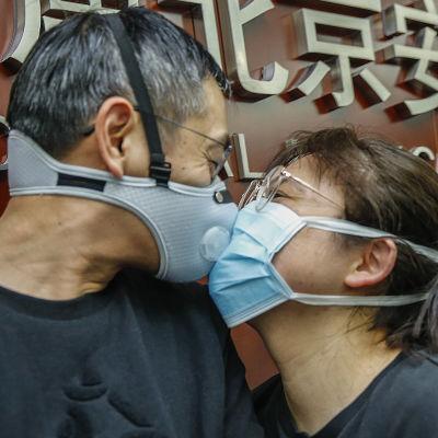 Två personer med munskydd pussar varandra.