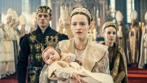 Nuori herttuatar katsoo eteenpäin vauva sylissään. Takana näkyy kirkko, molemmin puolin mies ja nainen sekä väkijoukkoa.