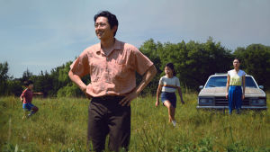 Jacob (Steven Yeun) och hans fru Monica (Yeri Han) och barnen David och Anne står på ett grönt fält, Jacob ser glad och nöjd ut.