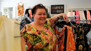 Företagaren Erica Wickman står vid en klädställning i sin kombinerade klädbutik och syateljé