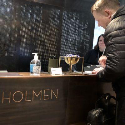 Manlig hotellgäst skriver in sig på Hanaholmen, handsprit i flaska på disken