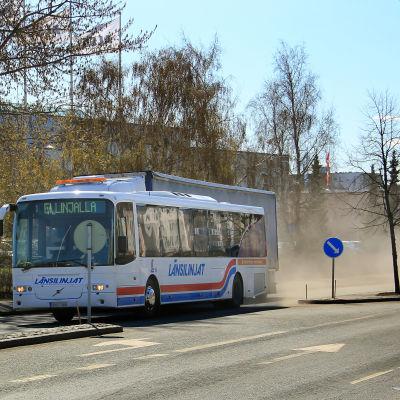 Buss drar uppdammoln efter sig.