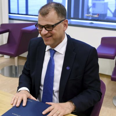 Juha Sipilä sitter bakom ett bord och skrattar.