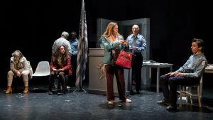 Teaterscen med en polisstation och en kvinna som håller i en handväska.