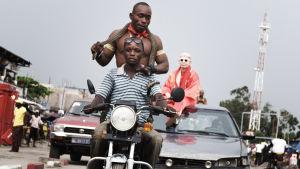35 lehmää ja yksi Kalashnikov. Kuvassa Mwimba Texas (albiino) ja tunnistamattomia tyyppejä Kinshasassa. Dokumenttielokuva, ohjaus Ossie von Richthofen..