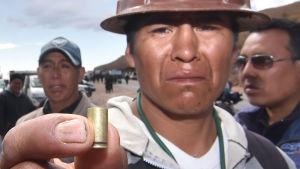 Gruvarbetare visar hylsa efter att polisen dödade två strejkande kolleger i Panduro.