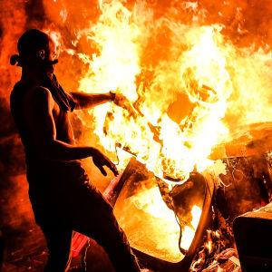 En demonstrant kastar ett föremål in i en eld. Demonstranter i Hamburg protesterar mot G20-mötet.