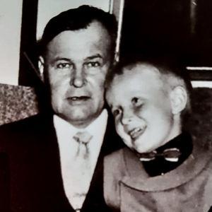 Pieni poika 50-luvun kuvassa istuu onnellisesti hymyillen nojatuolissa istuvan keski-ikäisen miehen sylissä ja nojaa tämän rintaan.