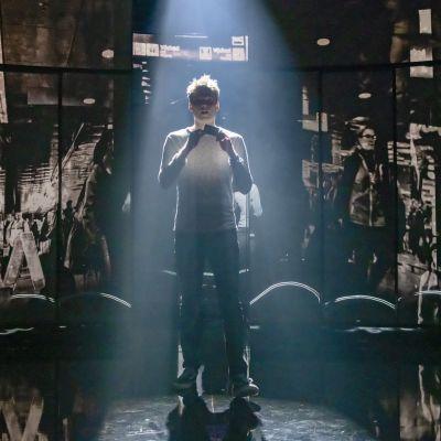 En ung skådespelare står på en teaterscen i starkt motljus.