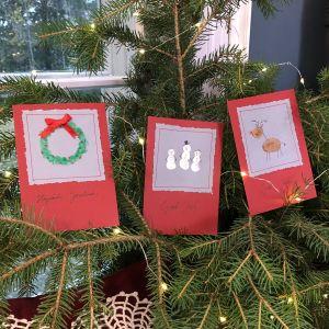 Kolme käsintehdyt joulukortit kuusenoksilla.