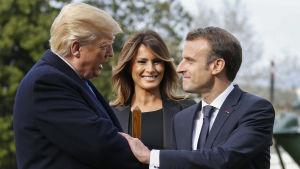 Presidenterna Emmanuel Macron och Donald Trump skakar hand medan Melania Trump ser på och ler.