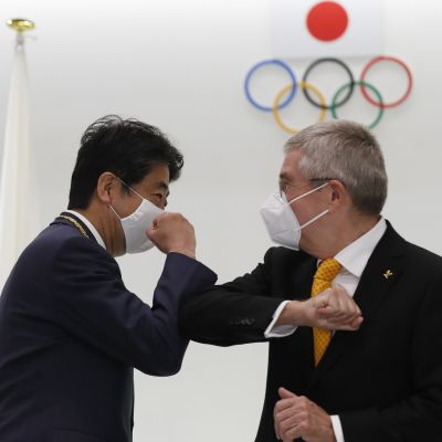 TOKYO, JAPAN - NOVEMBER 16: Japan's former Prime Minister Shinzo Abe and Thomas Bach, President of the International Olympic Committee (IOC), elbow bump after a ceremony to present the Olympic Order to Abe at Japan Olympic Museum on November 16, 2020 in Tokyo, Japan. Bach visits to Japan to discuss on the postponed Tokyo Olympic and Paralympic Games due to novel coronavirus pandemic. (