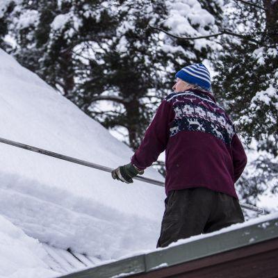 En man sopar ner snö från sitt tak.