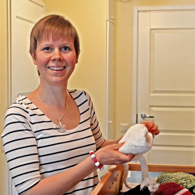 Eveliina Lindell håller upp en mössa i handen.