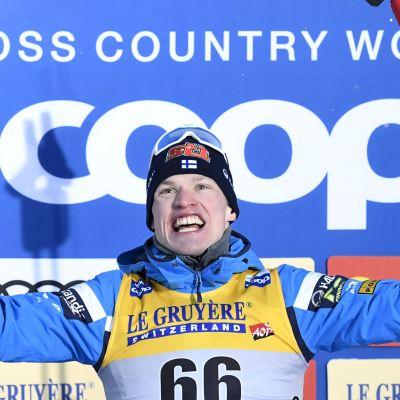Iivo Niskanen jublar på prispodiet med skidorna i ena handen, stavarna i andra.