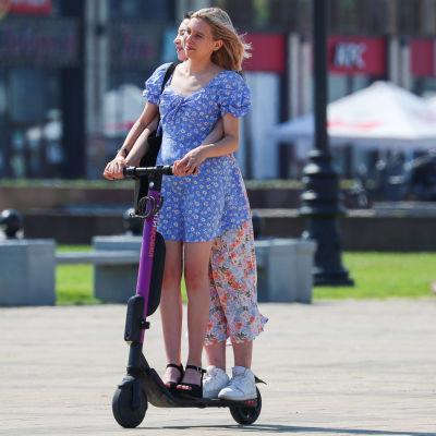 Två flickor på en elsparkcykel.
