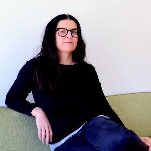 Micaela Röman sitter på en grön soffa och ler till kameran