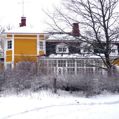 Villa Snäcksund, gulmålad trävilla, i vinterskrud