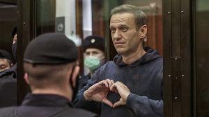 En man klädd i grå munkjacka formar sina händer till ett hjärta. Bakom och framför honom står män iklädda baretter och svarta munskydd.