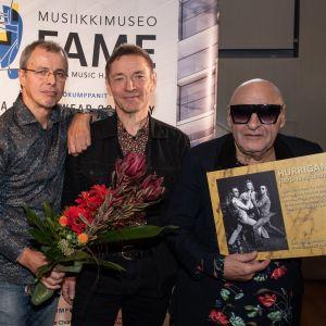 Remu Aaltonen, Ile kallio och Janne Louhivuori poserar med en blombukett och med en Hurriganes-plansch. Remu har solglasögon på sig.
