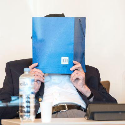 Koncentrationslägervakten Bruno Dey gömmer ansiktet under sin rättegång i Hamburg.