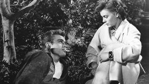 James dean ligger och röker, Natalie Wood ser på honom i vit kappa