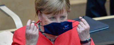 Angela Merkel sätter på sig ett munskydd med tysk EU-logo.