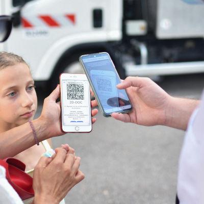 En kvinna med munskydd visar upp sin telefon och sitt digitala coronapass för en kontrollant. I mitten syns en ung flicka som ser på.