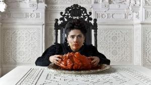 Nainen istuu valkoisen pöydän äärellä mustassa tuolissa naamassaan verta ja edessään lihakimpale.