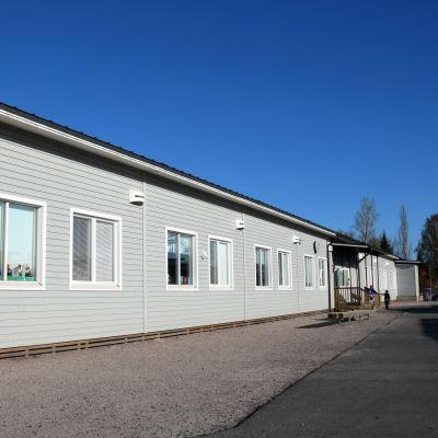 En ljusgrå skolbyggnad.