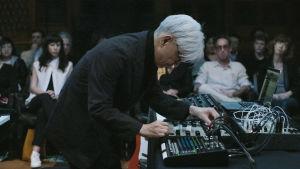 Ryuichi Sakamoto konsertissa elektronisen laitteen äärellä. Kuva async-konsertista..