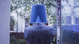 Ryuichi Sakamoto selin ämpäri päässä. Kuva dokumenttielokuvasta Coda.