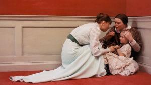 Kaksi naista ja nuori tyttö käytävän nurkassa. Kuva elokuvasta Kuiskauksia ja huutoja.