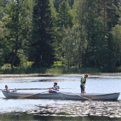 två stadsroddbåtar ute på sjön i Gallträsk. två personer sitter i en båt och en person står i en annan.