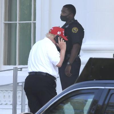 Trump puhuu kännykkään. Taustalla seisoo poliisi.