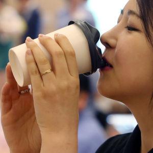 Sydkoreansk kvinna dricker kaffe ur en engångsmugg med ansiktsformat lock.
