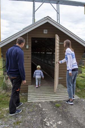 Ett barn springer in i ett lågt avlångt hus (skugghus) och en man och en kvinna följer efter.