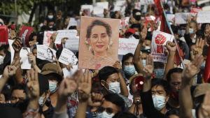 En folkmassa demonstrerar med plakat och med uppsträckta händer. De bär munskydd.