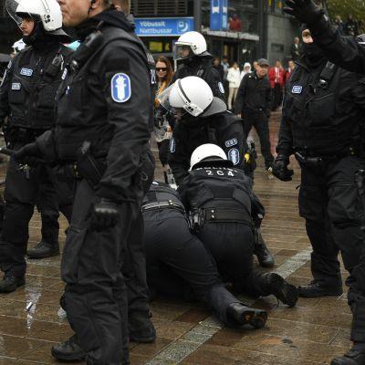 Polisen griper en antifascistisk demonstrant.