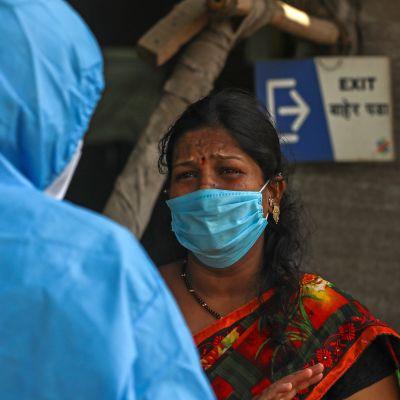 Vakavailmeinen nainen kuuntelee suojapukuista henkilöä maski kasvoillaan.