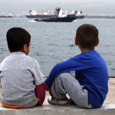 Två pojkar sitter vid havet utanför ett flyktingläger i Grekland.