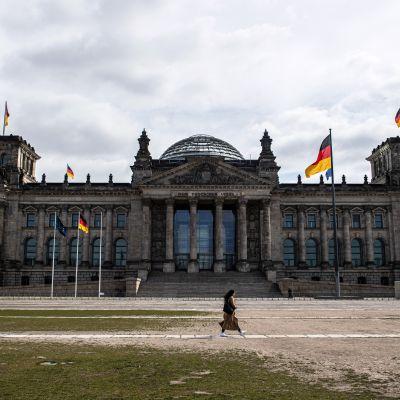 Nainen kävelee parlamenttirakennus Reichstagin edustalla koronan hiljentämässä Berliinissä. Suositut turistikohteet ovat nyt autioita.