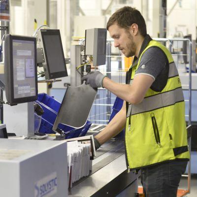 En anställd vid Posten, iklädd gul väst, sorterar post framför en bildskärm i Postens logistikcentral.