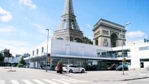 Fotomontage. Låg vit byggnad med Eiffeltornet och Triumfbågen i bakgrunden.