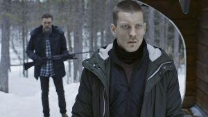 Polisen Lasse har smugit upp bakom Jaakko. Med geväret laddat.
