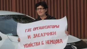 """""""Var är organisatörerna och betalarna av mordet på Boris Nemtsov"""" står det på den här kvinnans plakat. Hon demonstrerade utanför rättegångssalen i Moskva 3.10.2016."""