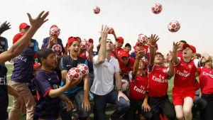 Martin Keown och flyktingar kastar bollar upp i luften.
