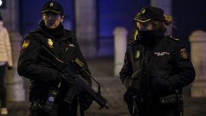 Två tungt beväpnade poliser vaktar över festligheterna i Madrid.