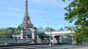 Järnvägsspår med bro och ett fotomontage av Eiffeltornet i bakgrunden.